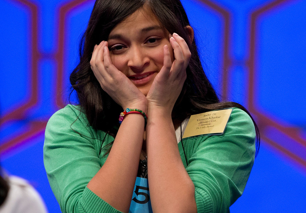""". Vismaya Kharkar, 14, of Bountiful, Utah, reacts as she takes her seat after spelling her word \""""temenos\"""" during the final round of the National Spelling Bee on Thursday, May 30, 2013, in Oxon Hill, Md. (AP Photo/Evan Vucci)"""