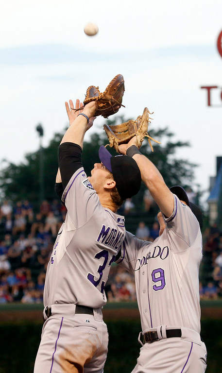 . Colorado Rockies first baseman Justin Morneau (33) and second baseman DJ LeMahieu eye a pop up by Chicago Cubs\' Starlin Castro during the first inning of a baseball game Tuesday, July 29, 2014, in Chicago. Morneau makes the catch on the play. (AP Photo/Charles Rex Arbogast)