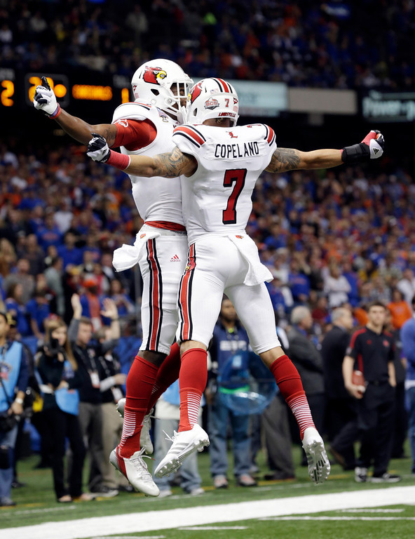 . Louisville wide receiver DeVante Parker, rear, celebrates with wide receiver Damian Copeland (7) after catching a touchdown pass in the first half of the Sugar Bowl NCAA college football game against Florida on Wednesday, Jan. 2, 2013, in New Orleans. (AP Photo/Dave Martin)