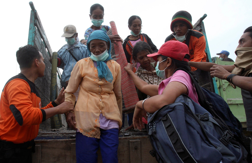 . Villagers get off a truck upon arrival at a temporary shelter after being evacuated from their homes on the slope of Mount Kelud, in Blitar, Friday, Feb. 14, 2014.  (AP Photo/Trisnadi)