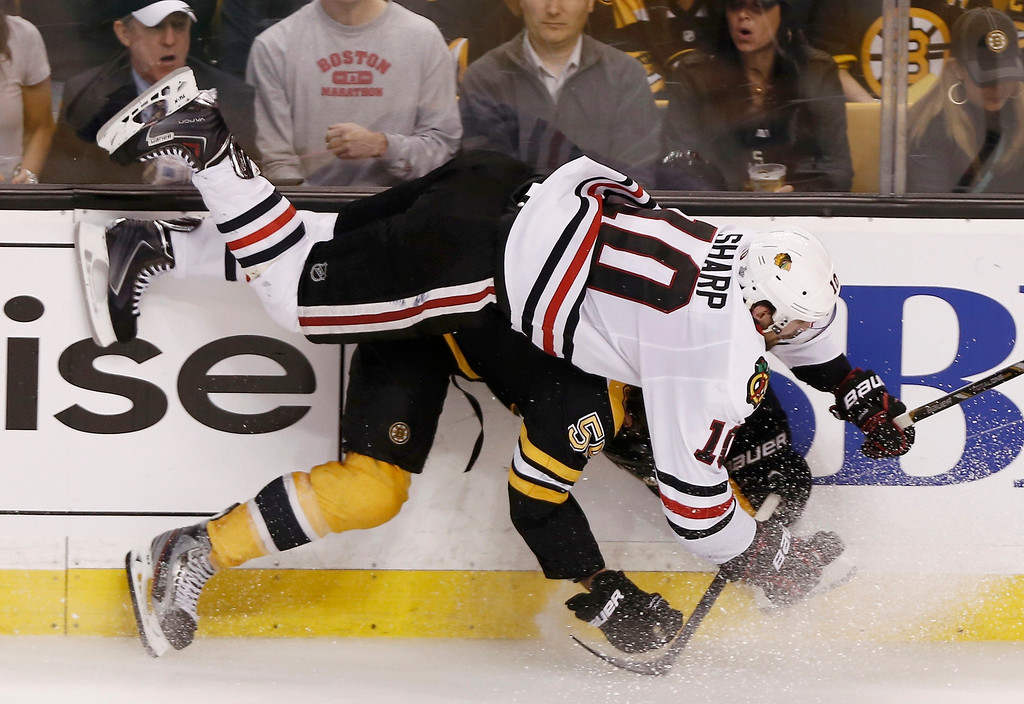 . Chicago Blackhawks\' Patrick Sharp (10) flies over Boston Bruins\' Johnny Boychuk during the third period in Game 4 of their NHL Stanley Cup Finals hockey series in Boston, Massachusetts, June 19, 2013. REUTERS/Winslow Townson