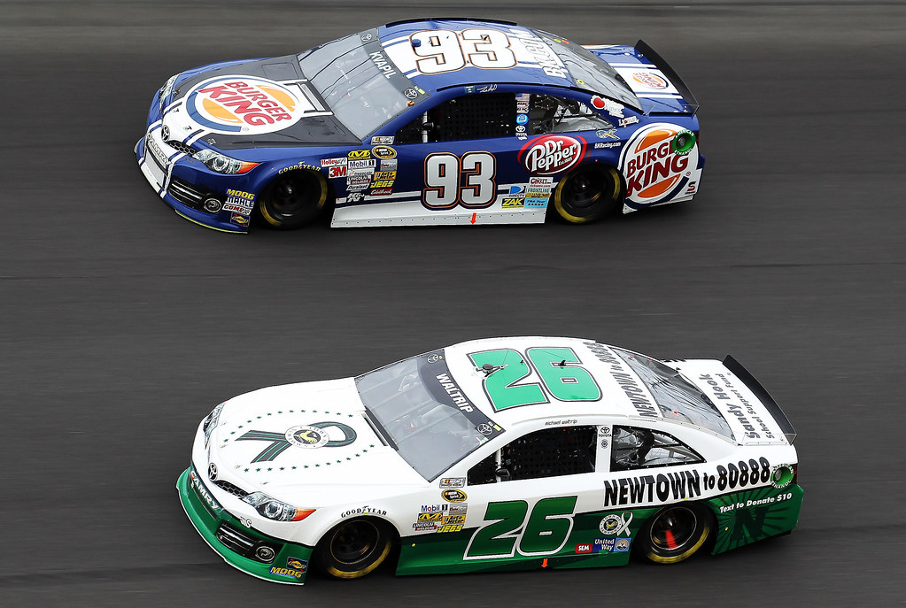 . Michael Waltrip, driver of the #26 Sandy Hook School Support Fund Toyota, and Travis Kvapil, driver of the #93 Burger King/Dr. Pepper Toyota, race during the NASCAR Sprint Cup Series Daytona 500 at Daytona International Speedway on February 24, 2013 in Daytona Beach, Florida.  (Photo by Todd Warshaw/Getty Images)