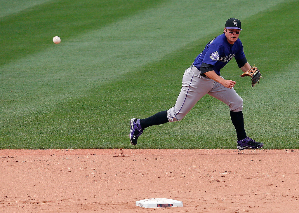 . Josh Rutledge #14 of the Colorado Rockies cannot field a grounder that bounced off of second base from the bat of Daniel Nava #29 of the Boston Red Soxx in the 1st inning at Fenway Park on June 26, 2013 in Boston, Massachusetts.  (Photo by Jim Rogash/Getty Images)
