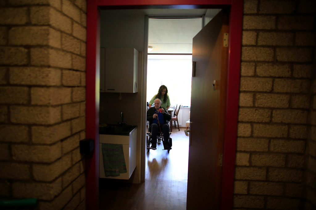 . Spanish nurse Maria Jose Marin, 23, pushes a man in a wheelchair through the Deo Gratias nursing home in The Hague, June 7, 2013. After months of studying Dutch, a group of young Spanish nurses moved to the Netherlands to take up work, fleeing a dismal job market at home. Spain\'s population dropped last year for the first time on record as young professionals and immigrants who moved here during a construction boom head for greener pastures. Spain\'s jobless rate is 27 percent, and more than half of young workers are unemployed. For Spanish nurses, the Netherlands\' nursing deficit is a boon. Picture taken June 7, 2013.  REUTERS/Marcelo del Pozo