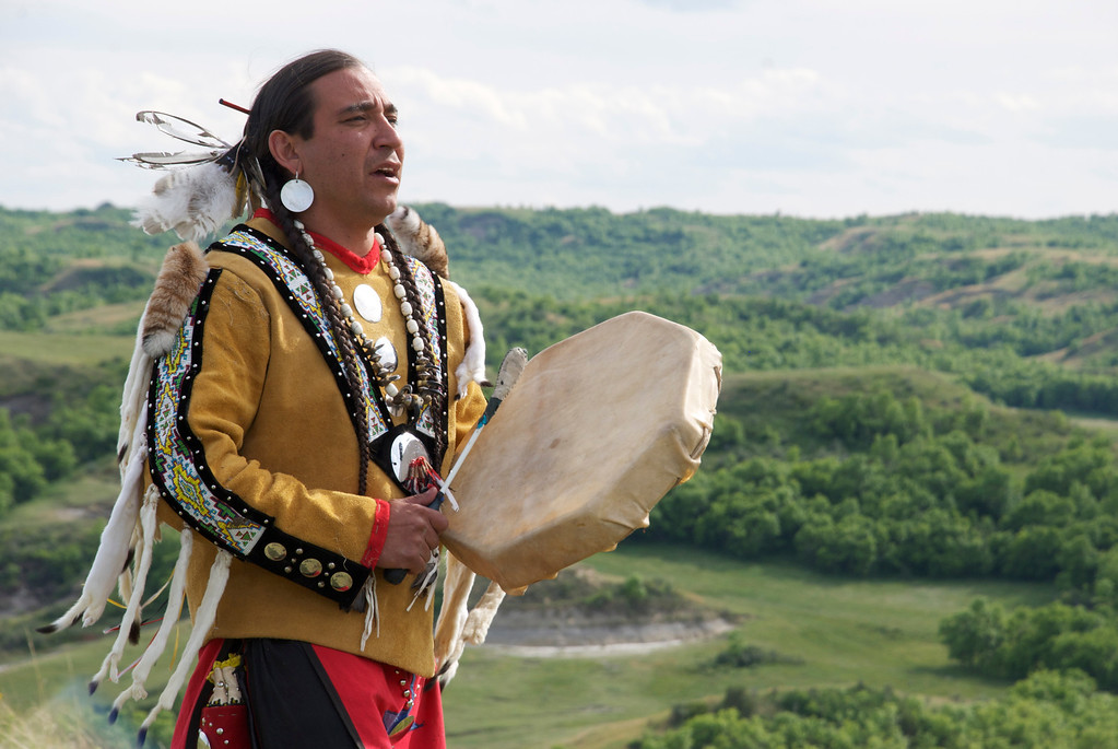 . Allan Demaray, Mandan Native American,  standing on butte playing traditional drum and singing as part of pit-trapping ceremony. (photo credit: © NGT )