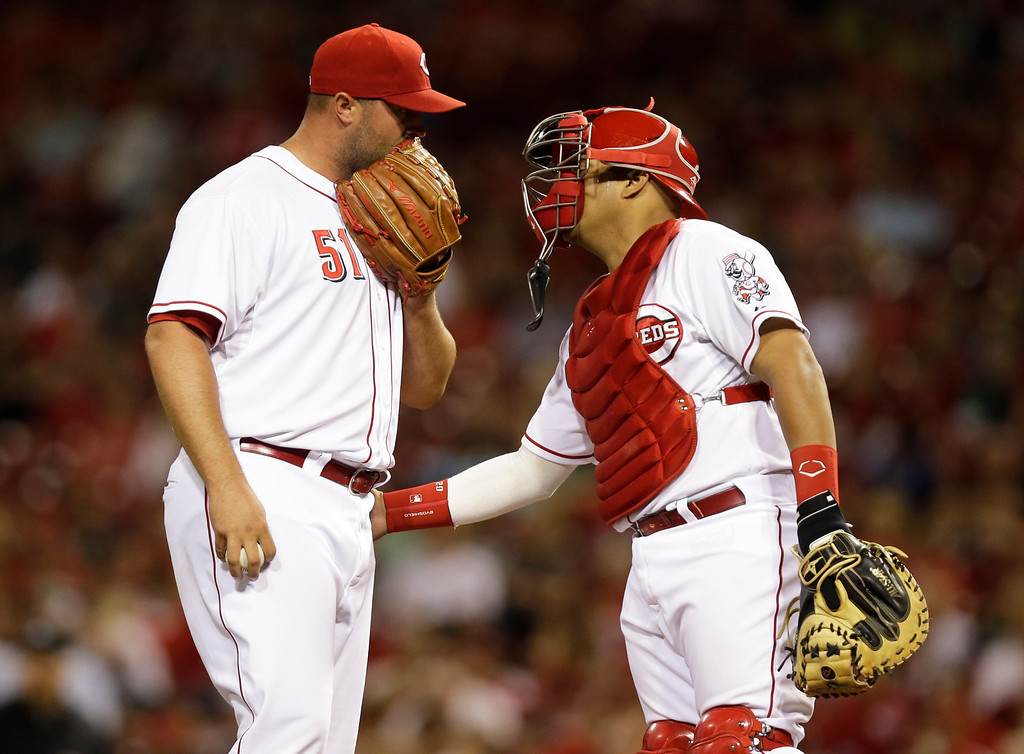 . Cincinnati Reds relief pitcher Jonathan Broxton (51) talks with catcher Brayan Pena in the ninth inning of a baseball game against the Colorado Rockies, Friday, May 9, 2014, in Cincinnati. Broxton was the winning pitcher in the game won by Cincinnati 4-3. (AP Photo/Al Behrman)