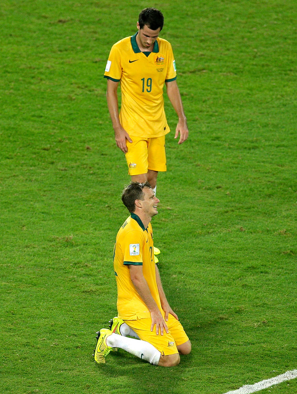. Australia\'s Ryan McGowan, top, stands in dejection after Chile scored during the group B World Cup soccer match between Chile and Australia in the Arena Pantanal in Cuiaba, Brazil, Friday, June 13, 2014. (AP Photo/Michael Sohn)