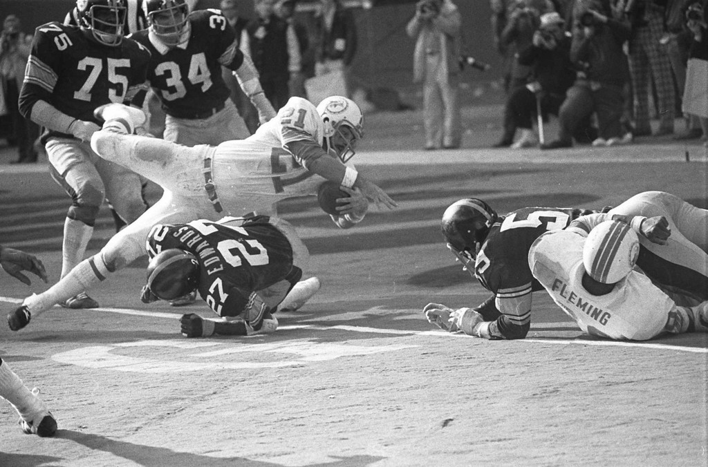 """. Miami Dolphins Jim Kiick goes headfirst over Pittsburgh Steelers\"""" Glen Edwards Dec. 31, 1972 as Kiick scores in third quarter of the AFC championship game at Pittsburgh\'s Three Rivers Stadium. (AP Photo)"""