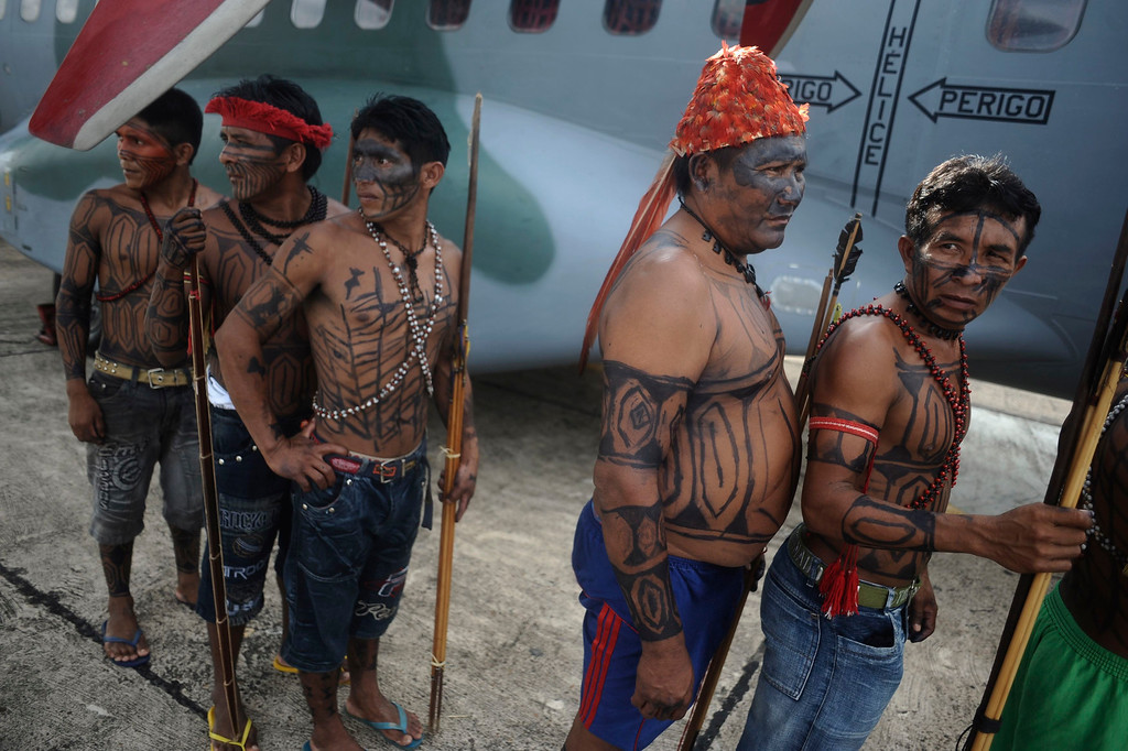 . Munduruku Indians, many flying for the first time, board a Brazilian Air Force plane to fly to Brasilia for talks with the government, in Altamira June 4, 2013. Air Force planes flew 144 Munduruku Indians to Brasilia for talks to end a week-long occupation of the controversial Belo Monte dam on the Xingu River, a huge project aimed at feeding Brazil\'s fast-growing demand for electricity. REUTERS/Lunae Parracho