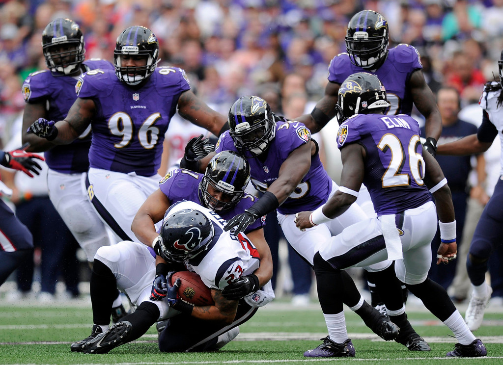 . Houston Texans running back Arian Foster, bottom, is tackled by a pack of Baltimore Ravens defenders in the first half of an NFL football game Sunday, Sept. 22, 2013, in Baltimore. (AP Photo/Nick Wass)