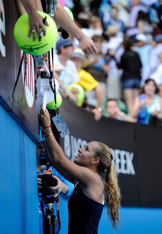 . Dominika Cibulkova of Slovakia signs autographs for fans after defeating Agnieszka Radwanska of Poland during their semifinal at the Australian Open tennis championship in Melbourne, Australia, Thursday, Jan. 23, 2014. (AP Photo/Andrew Brownbill)