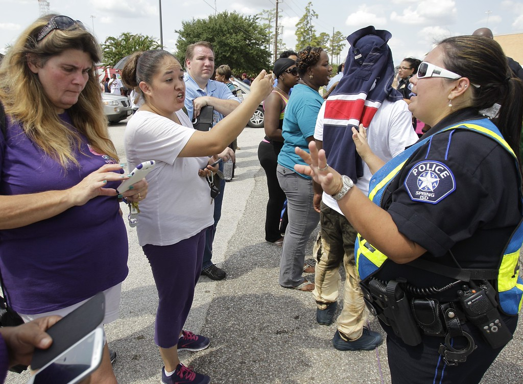 . A Spring ISD police officer talks to parents outside Spring High School after at least one person was killed and others were injured during an altercation inside Spring High School Wednesday, Sept. 4, 2013, morning in Spring, Texas. The stabbing happened about 7 a.m. on the campus at 19428 North Freeway, according to the Harris County Sheriff\'s Office. (AP Photo/Houston Chronicle, Melissa Phillip)