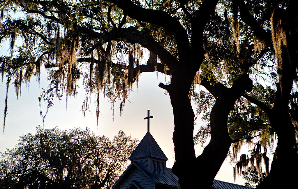 . The sun rises behind St. Luke Baptist Church in the Hog Hammock community of Sapelo Island, Ga. on Friday, May 17, 2013. Roughly 47 residents, most of them descendants of West African slaves known as Geechee, remain on the coastal Georgia island where their ancestors were brought to work a plantation in the early 1800s. Isolated over time to the Southeast\'s barrier islands, the Geechee of Georgia and Florida, otherwise known as Gullah in the Carolinas, have retained their African traditions more than other African American communities in the U.S. Once freed, the slaves were able to acquire land and created settlements on the island, of which only the tiny 464-acre Hog Hammock community still exists. Residents say a sudden tax hike, lack of jobs, and development is endangering one of the last remaining Geechee communities from Florida to North Carolina. (AP Photo/David Goldman)