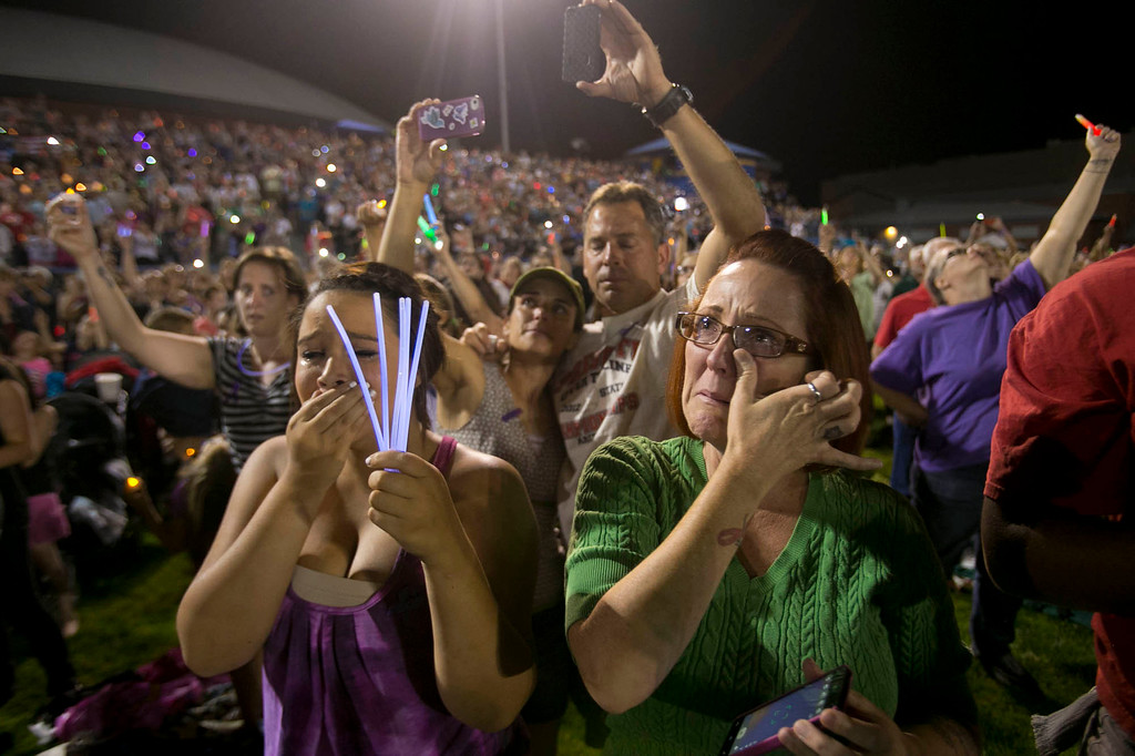 . Noelle Ewing, right, of Prescott Valley, Ariz. cries alongside her daughter, Keira Ewing, 15, during a candlelight vigil for the 19 firefighters killed battling the Yarnell Hill Fire, on the football field at Prescott High School in Prescott, Ariz. on Tuesday, July 2, 2013. (AP Photo/The Arizona Republic, David Wallace)