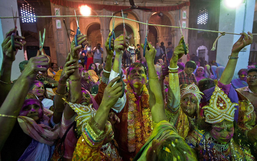. Sulabh International Founder Bindeshwari Pathak (C) and Indian widows, some dressed as Hindu gods Radha and Krishna, cut a string symbolizing the breaking of tradition where widows are not allowed to celebrate Holi, during celebrations in Vrindavan on March 14, 2014.  AFP PHOTO/Prakash SINGH/AFP/Getty Images
