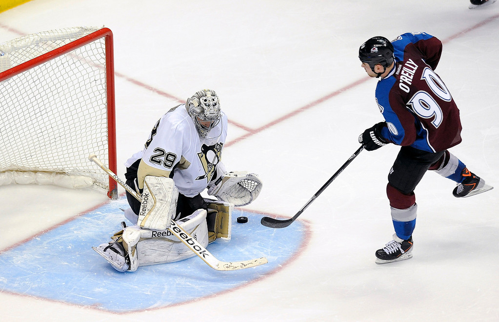 . Pittsburgh Penguins goalie Marc-Andre Fleury, left, makes a save against Colorado Avalanche center Ryan O\'Reilly, right, in the shootout of an NHL hockey game Sunday, April 6, 2014, in Denver. The Penguins won 3-2. (AP Photo/Chris Schneider)