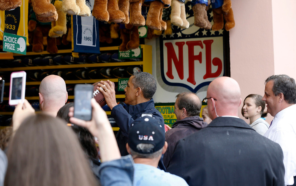 . U.S. President Barack Obama throws a football at a sideshow arcade game alongside New Jersey Governor Chris Christie (R ) at Point Pleasant in New Jersey, May 28, 2013.  REUTERS/Jason Reed
