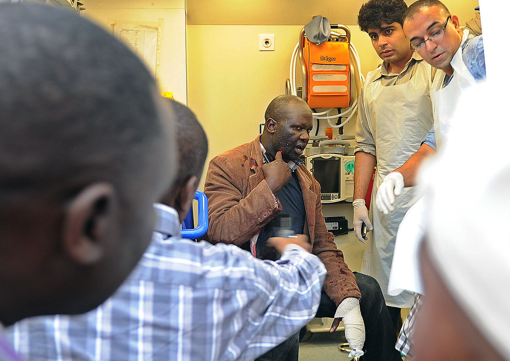 . An injured security official talks to his colleagues as he is evacuated in an ambulance on September 21, 2013, following a security operation at an upmarket shopping mall in Nairobi where suspected terrorists engaged Kenyan security forces in a drawn out gun fight. Some 20 people have been killed and about 50 wounded Saturday in the initial attack by the gunmen the Kenya Red Cross said.  AFP PHOTO / Tony KARUMBA/AFP/Getty Images