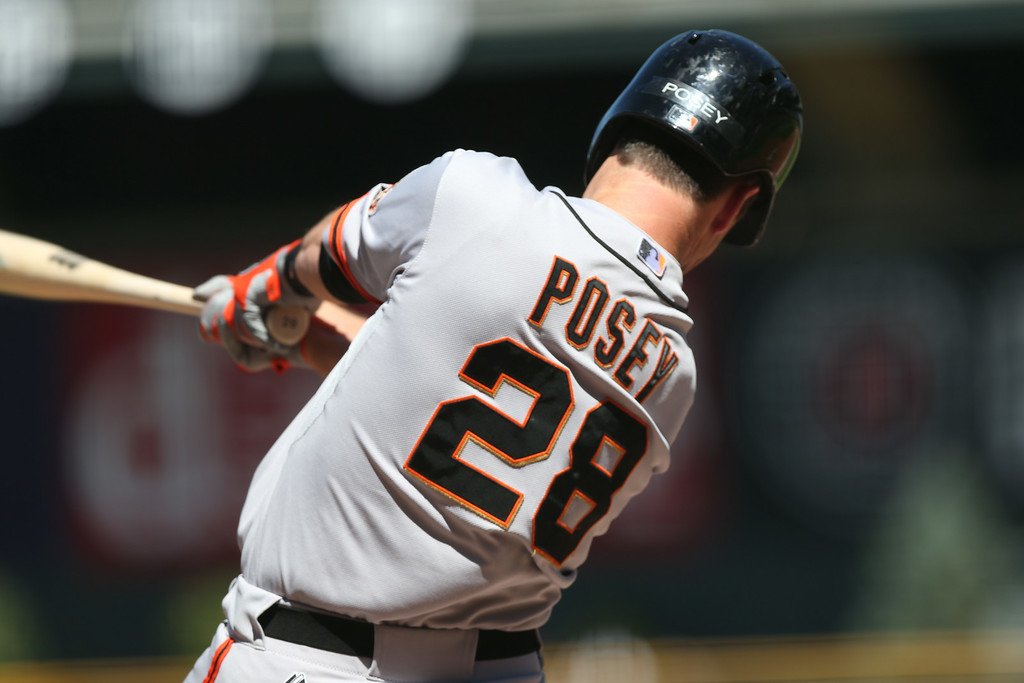 . San Francisco Giants\' Buster Posey follows the flight of his sacrifice fly to drive in a run against the Colorado Rockies in the first inning of a baseball game in Denver on Wednesday, Sept. 3, 2014. (AP Photo/David Zalubowski)