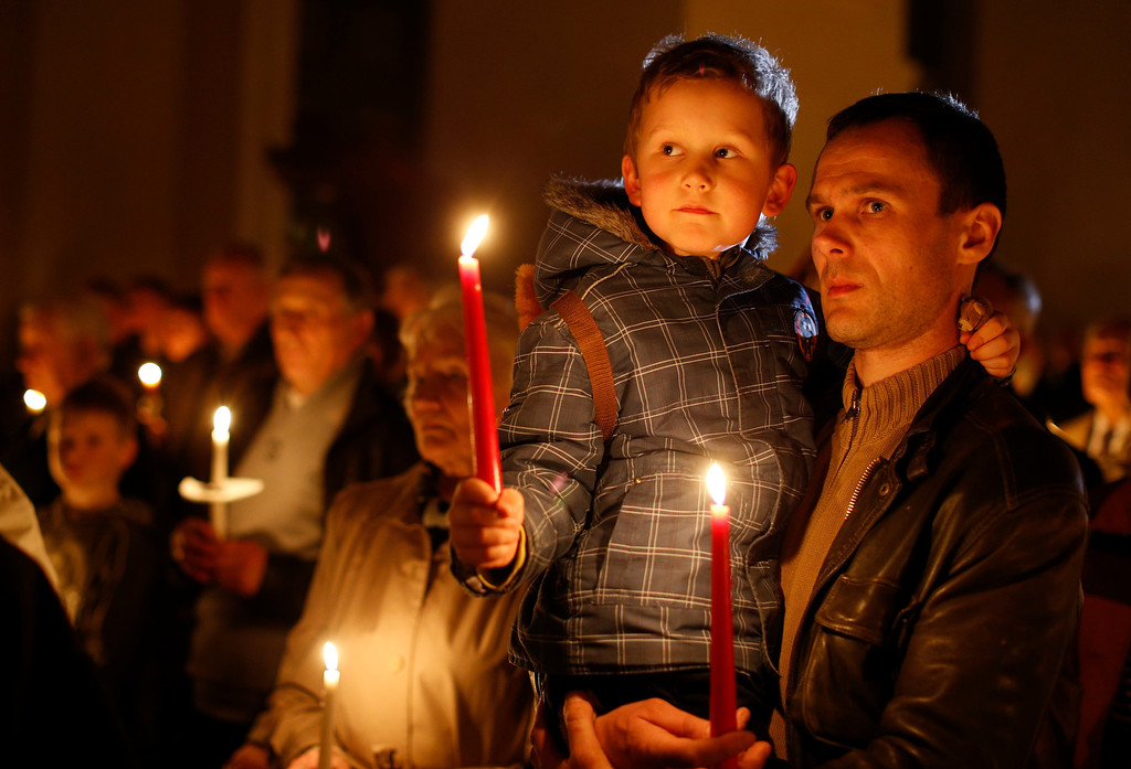 . Worshippers hold candles during the Easter vigil mass in Cathedral-Basilica at the Vilnius, Lithuania, Saturday, April 19, 2014. (AP Photo/Mindaugas Kulbis)
