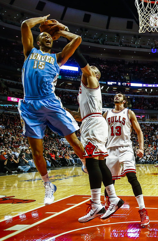 . Chicago Bulls forward Carlos Boozer (C) tries to block a shot by Denver Nuggets forward Anthony Randolph (L) as Chicago Bulls center Joakim Noah (R) watches in the second half of their NBA game at the United Center in Chicago, Illinois, USA, 21 February 2014. The Bulls defeated the Nuggets.  EPA/TANNEN MAURY