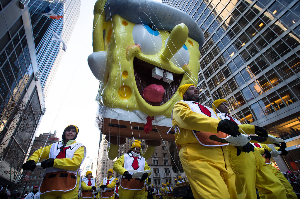 . A giant Spongebob Squarepants balloon is marched down 6th Avenue during the 87th Annual Macy\'s Thanksgiving Day Parade, Thursday, Nov. 28, 2013, in New York. After fears the balloons could be grounded if sustained winds exceeded 23 mph, Snoopy, Spider-Man and the rest of the iconic balloons received the all-clear from the New York Police Department to fly between Manhattan skyscrapers on Thursday. (AP Photo/John Minchillo)