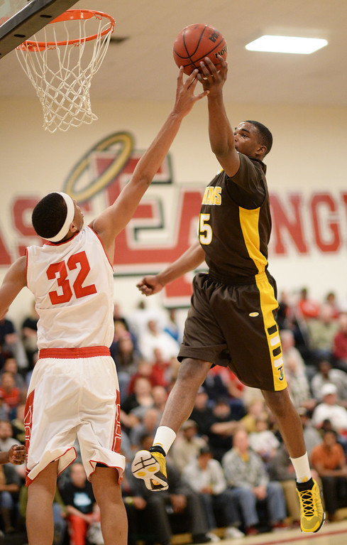 . DENVER, CO. JANUARY 24: Treyvon Andres of Thomas Jefferson High School (15) scores over Tyre Robinson of East High School (32) during the 1st half of the game at East High School in Denver, Colorado January 24, 2014. East High School won 91-62. (Photo by Hyoung Chang/The Denver Post)