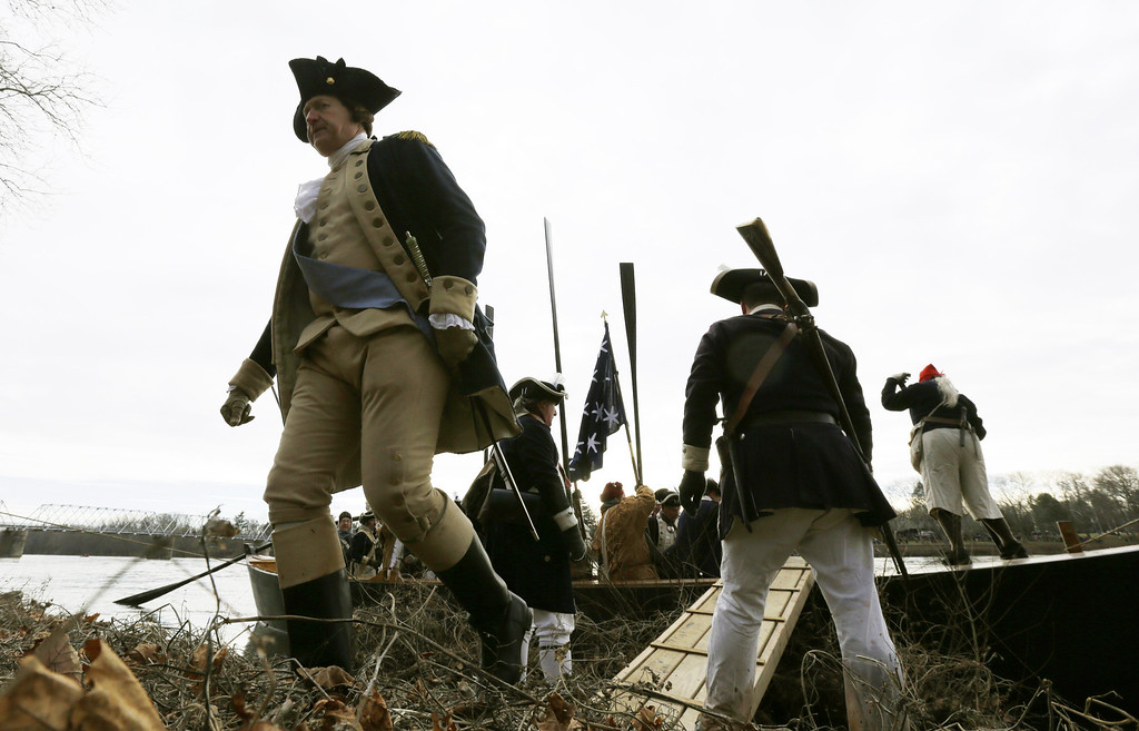 . George Washington, played by John Godzieba, left, walks onto land on the New Jersey side after a crew of re-enactors crossed the Delaware River on a boat from Pennsylvania during the 61st annual re-enactment of Washington\'s daring Christmas 1776 crossing of the river, the trek that turned the tide of the Revolutionary War, in Washington Crossing, N.J. During the crossing 237 years ago, boats ferried 2,400 soldiers, 200 horses and 18 cannons across the river, and the troops marched eight miles downriver before battling Hessian mercenaries in the streets of Trenton. (AP Photo/Julio Cortez)