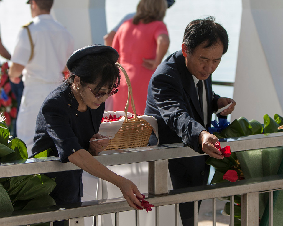 . Japanese Consul General Toyoei Shigeeda, right, and his wife, Michiko Shigeeda drop flowers pedals into the harbor aboard the USS Arizona Memorial during the ceremony commemorating the 72nd anniversary of the attack on Pearl Harbor, Saturday, Dec. 7, 2013, in Honolulu.  (AP Photo/Marco Garcia)