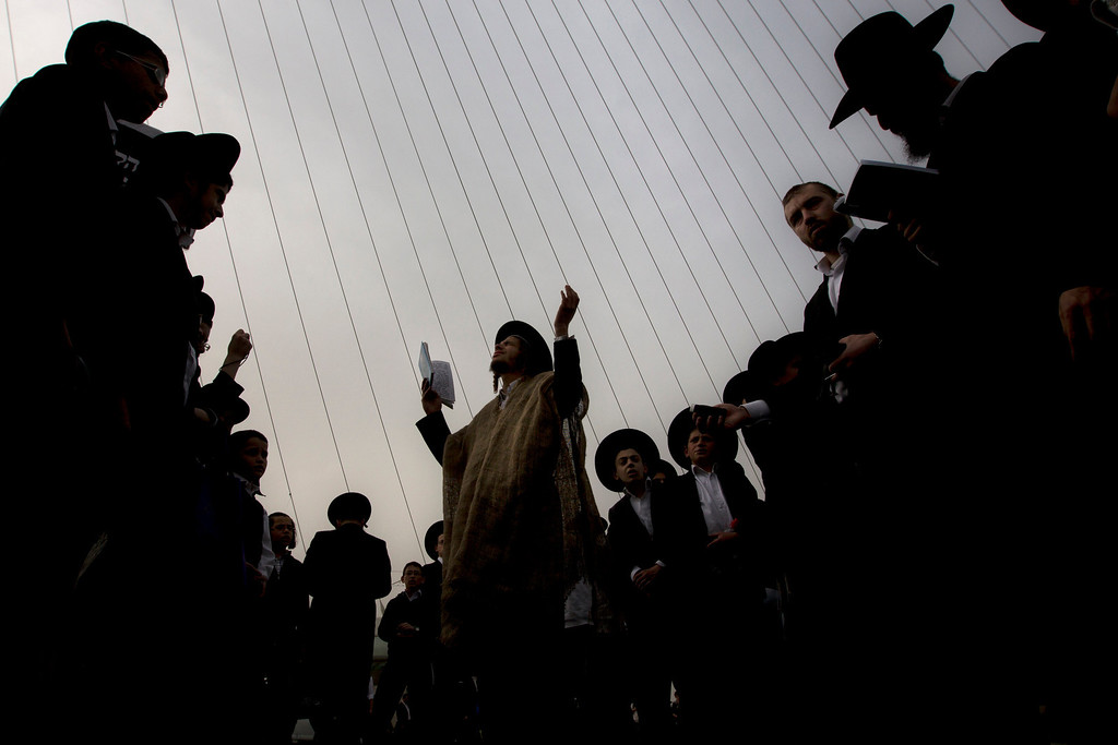 . Ultra-Orthodox Jewish men pray during a rally attended by hundreds of thousands against plans to force them to serve in the Israeli military, blocking roads and paralyzing the city of Jerusalem, Sunday, March 2, 2014. The widespread opposition to the compulsory draft poses a challenge to the country, which is grappling with a cultural war over the place of the ultra-Orthodox in Israeli society. With secular Jews required to serve, the issue is one of the most sensitive flashpoints between Israel\'s secular majority and its devout minority. (AP Photo/Sebastian Scheiner)