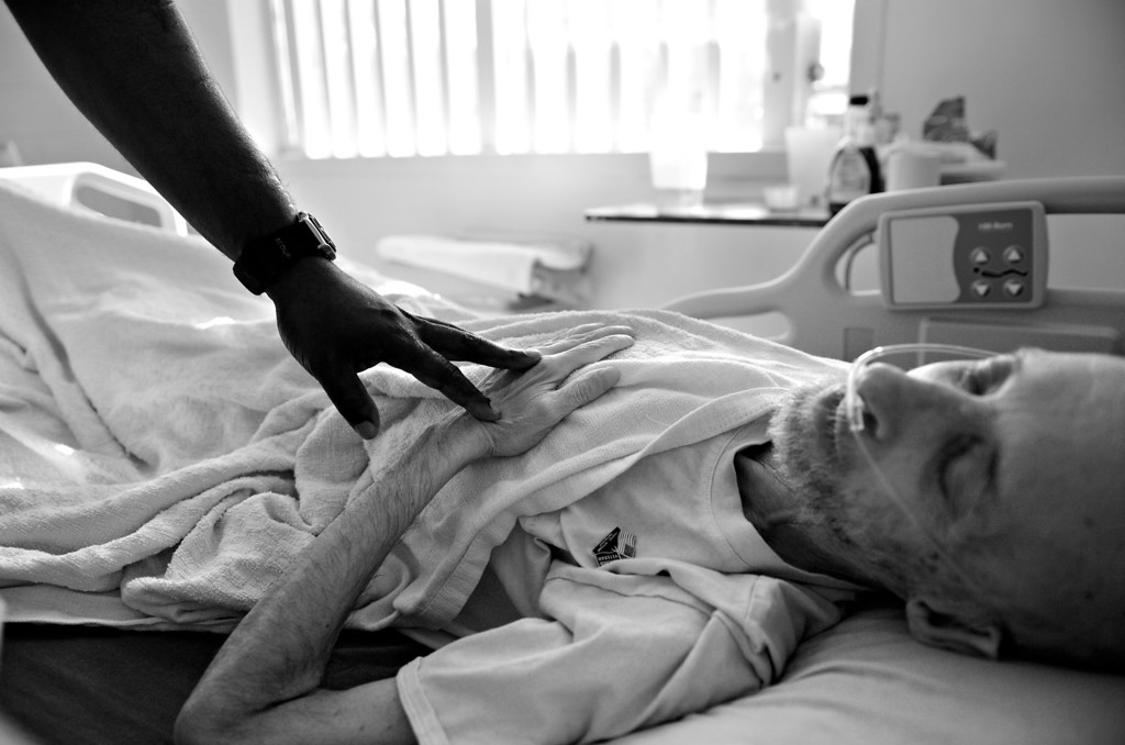 ". CANYON CITY, CO. - NOVEMBER 08: Wayne Rose, left, reaches out and touches Robert Bryan before leaving his room, November 08, 2012. ""Cancer finally caught up to me,\"" said Bryan. \""I feel good about dying. I have done lots of bad things in my life and there is nothing in this world for me anymore.\"" (Photo By RJ Sangosti/The Denver Post)"