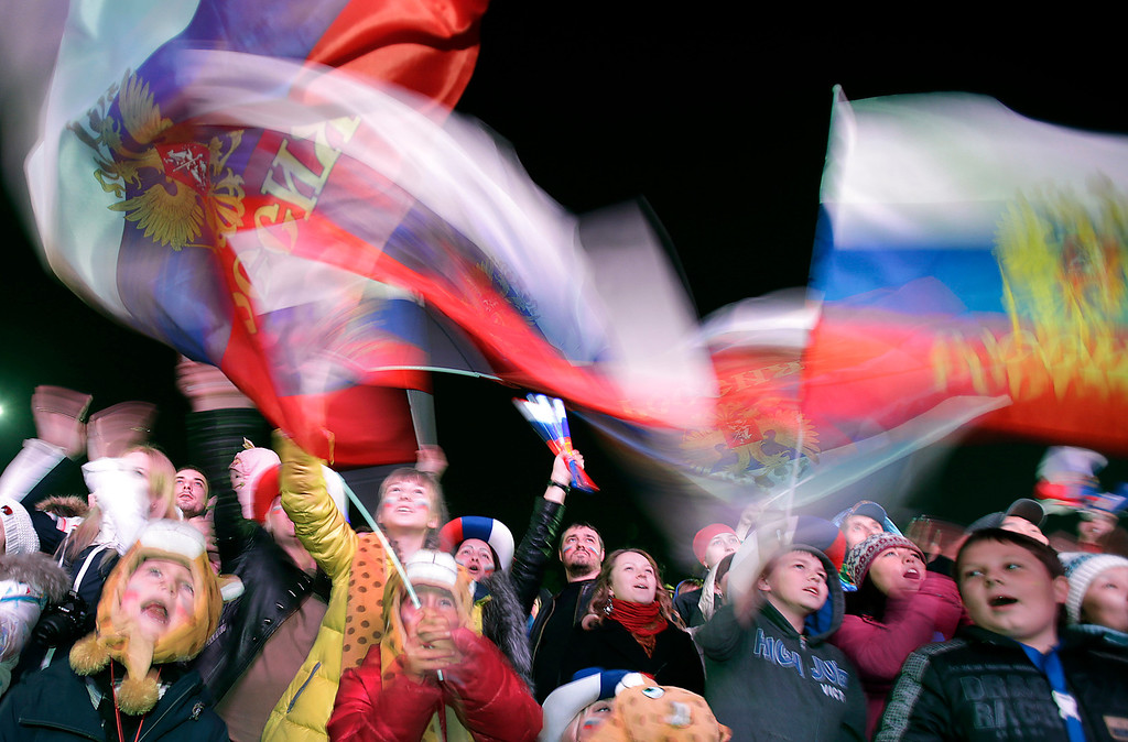 . Russian families gather and wave their national flag during the national anthem as they watch the live telecast of the 2014 Winter Olympics opening ceremony, Friday, Feb. 7, 2014, in downtown Sochi, Russia. (AP Photo/Wong Maye-E)