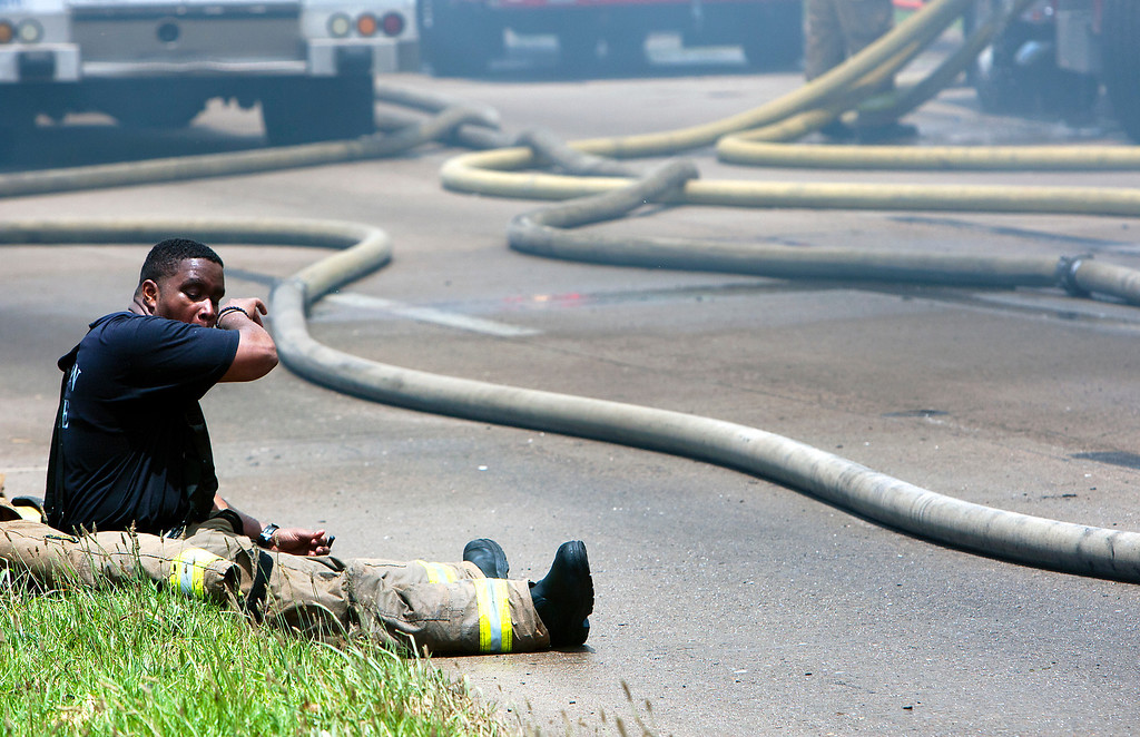 . A firefighter sits on the ground during a blaze at the Southwest Inn on U.S. 59 in Houston on Friday, May 31, 2013. (AP Photo/Houston Chronicle, Cody Duty)