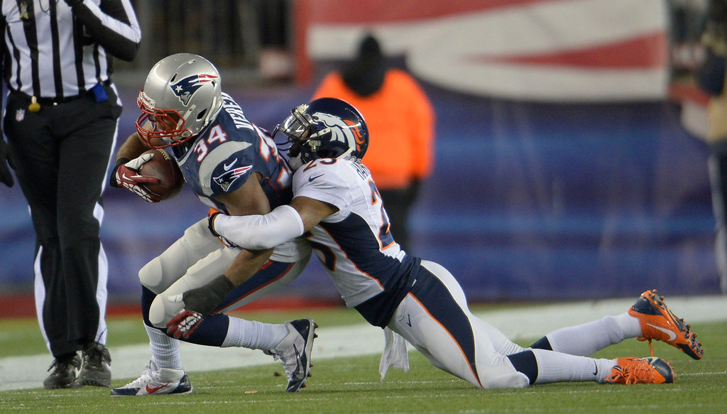 . Denver Broncos cornerback Chris Harris (25) makes a tackle on New England Patriots running back Shane Vereen (34) during the first quarter November 24, 2013 at Gillette Stadium. (Photo by Joe Amon/The Denver Post)