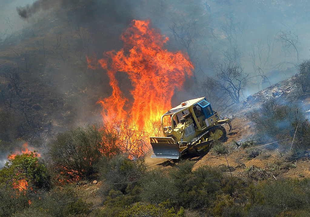 . A bulldozer clears a firebreak near a wildfire burning along a hillside near homes in Thousand Oaks, Calif., Thursday, May 2, 2013.  (AP Photo/Mark J. Terrill)