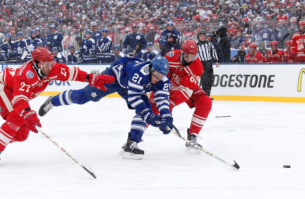 . James van Riemsdyk #21 of the Toronto Maple Leafs cuts in between Kyle Quincey #27 and Danny DeKeyser #65 of the Detroit Red Wings during the first period of the 2014 Bridgestone NHL Winter Classic at Michigan Stadium on January 1, 2014 in Ann Arbor, Michigan. (Photo by Gregory Shamus/Getty Images)