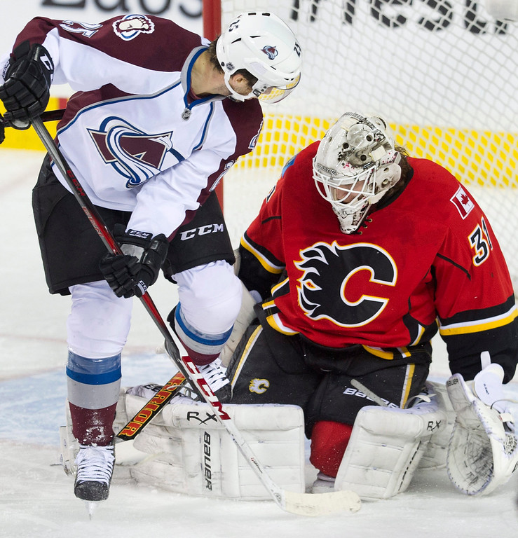 . Colorado Avalanche\'s Maxime Talbot, left, gets his skate caught in the pads of Calgary Flames goalie Karry Ram during the first period of an NHL hockey game, Friday, Dec. 6, 2013 in Calgary, Alberta. (AP Photo/The Canadian Press, Larry MacDougal)