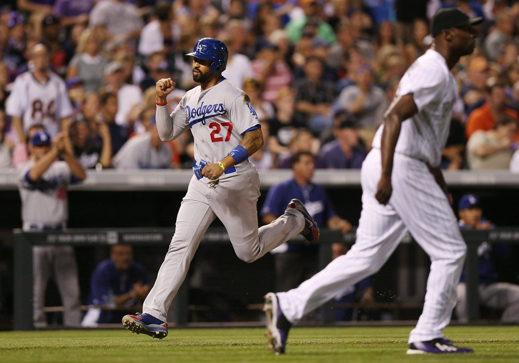 . Los Angeles Dodgers\' Matt Kemp (27) raises his fist as he scores the go-ahead run on a single by Juan Uribe as Colorado Rockies relief pitcher LaTroy Hawkins looks for the throw from the outfield in the ninth inning of the Dodgers\' 3-2 victory in a baseball game in Denver, Thursday, July 3, 2014. (AP Photo/David Zalubowski)