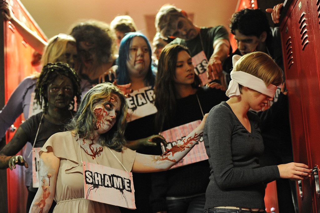 . BOULDER, CO- FEBRUARY 19:  Zombies listen to direction from the videographer during the filming of their video.   Zombie Phillipa Keosheyan, 14, middle, taunts main character Shawna Gustafson, 18, left.  With the help of a professional videographer, Fairview High School students produced a zombie video to advertise an Awareness Drive in Boulder Valley schools designed to bring attention to a variety of mental health and wellness issues.  Students were made to look like zombies by make-up artists from Theatrical Costumes, Etc. (Photo By Helen H. Richardson/ The Denver Post)