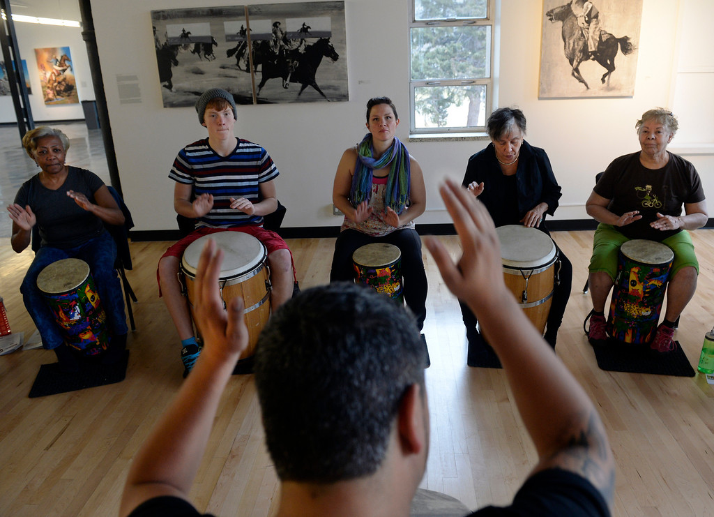 . DENVER, CO - FEBRUARY 15: Students watch carefully the drumming technique of their instructor Jose Daniel Beteta. In the background from left are Kathy Hayes, Smith Nagel, 14, and his mother Rachel, Juana Bordas, and Elda Munoz. Co-founders of Barrio E, Tamil Maldonado and husband Jose Daniel Beteta, gather students together at the McNichols Building in downtown Denver to teach a Bomba workshop. Bomba is an Afro-Caribbean rhythm with percussion, dance and song. Barrio E is a project based in Boulder that hopes to serve communities around Colorado and aims to expose, educate, and promote traditional Puerto Rican culture and music. Barrio E\'s next workshop for both kids and adults at McNichols will be Saturday, Mar. 15, 2014. (Photo by Kathryn Scott Osler/The Denver Post)