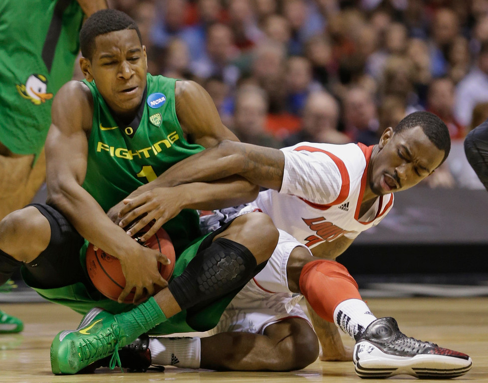 . Oregon guard Dominic Artis (1) and Louisville guard Russ Smith scramble for a loose ball during the second half of a regional semifinal in the NCAA college basketball tournament, Friday, March 29, 2013, in Indianapolis. (AP Photo/Darron Cummings)