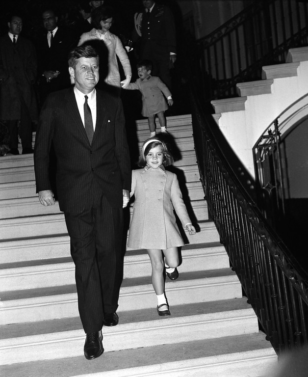 . President Kennedy leads Caroline down the portico steps, followed by the first lady with John Jr., for the Black Watch Regiment exhibition on the White House South Lawn on Nov. 13, 1963.  Associated Press file