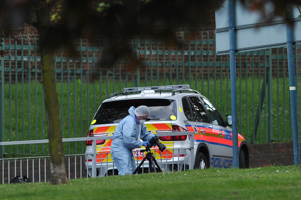 """. A police forensics officer takes photographs inside a cordoned off area in Woolwich, east London, on May 22, 2013, following an incident in which one man was killed and two others seruiously injured.  British police shot and wounded two men after a man thought to be a serving soldier was killed outside a London barracks, in an attack Prime Minister David Cameron called \""""truly shocking\"""". In a dramatic move, the government\'s emergency response committee was being summoned following the killing which some eyewitness reports suggested was an attempted beheading using machete-like knives.   AFP PHOTO / CARL COURTCARL COURT/AFP/Getty Images"""