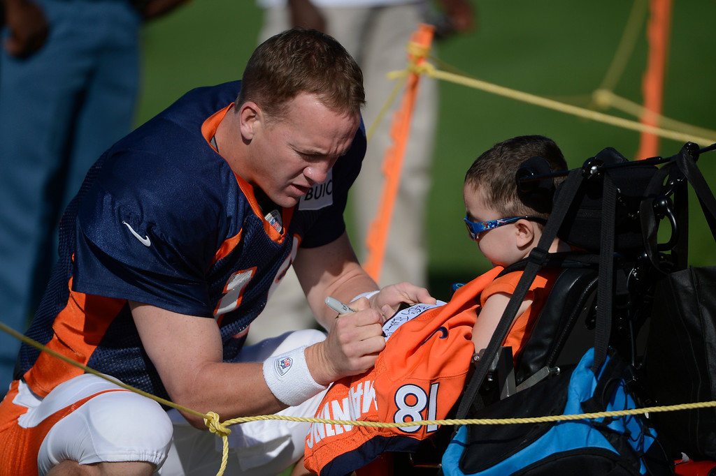 . ENGLEWOOD, CO - JULY 27: Denver Broncos QB, Peyton Manning signs a jersey for a young fan before the start of training camp at Dove Valley Saturday July 26, 2013.  (Photo By Andy Cross/The Denver Post)