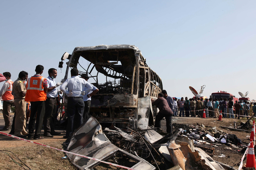 . Officials inspect the scene after a bus crashed into a highway barrier and erupted in flames at Mehabubnagar in southern Andhra Pradesh state, India, Wednesday, Oct. 30, 2013.  (AP Photo/Mahesh Kumar A.)