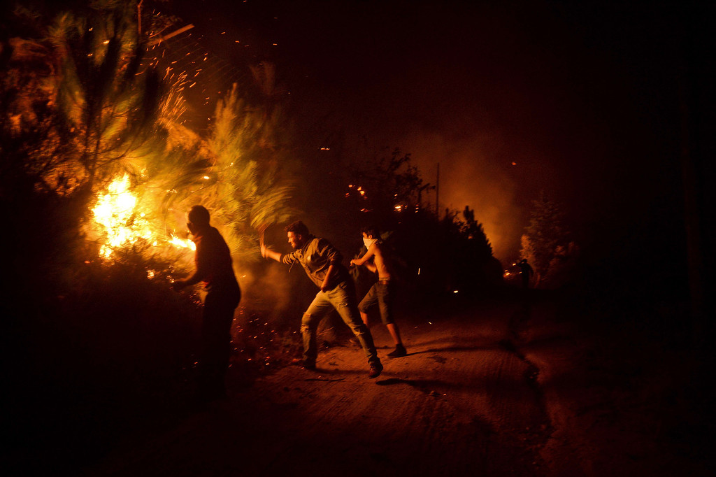 . People try to extinguish a wildfire approaching their houses in Santiago de Besteiros, near Caramulo, central Portugal, early on August 30, 2013.  AFP PHOTO / PATRICIA DE MELO MOREIRA/AFP/Getty Images