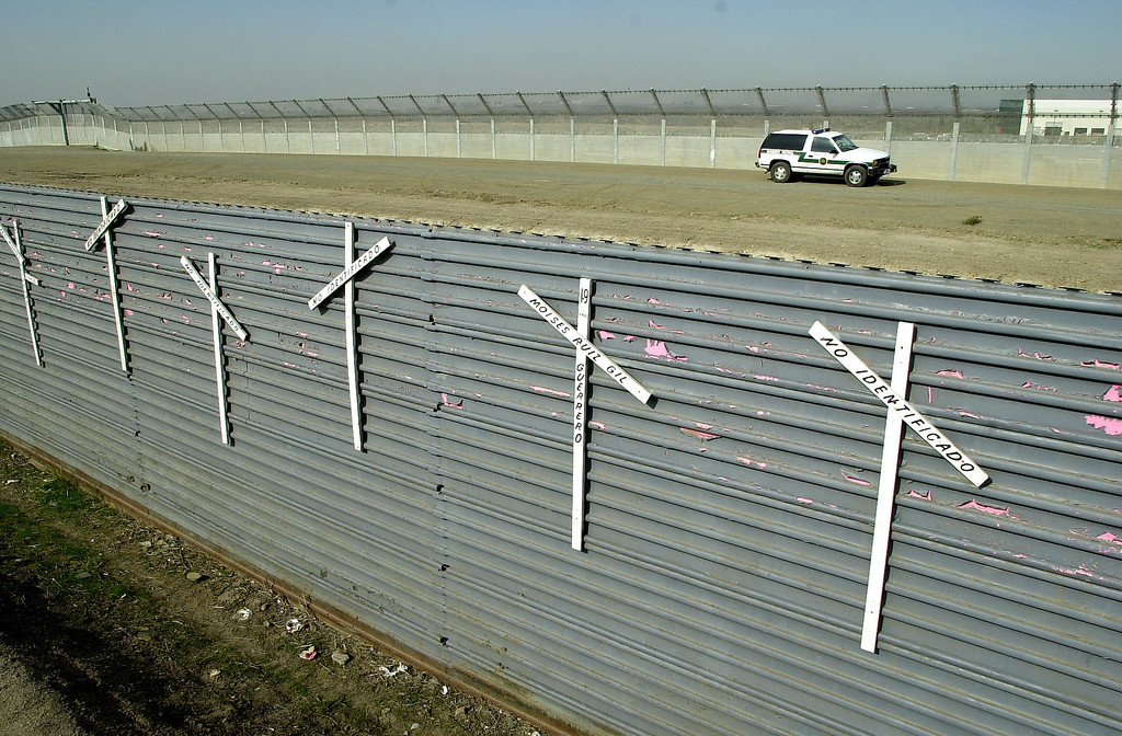 """. Crosses placed by human rights activists on a section of border wall that separates San Diego from Tijuana read \""""Unidentified\"""" in Spanish or bear the names of people who died while crossing to the United States on Wednesday, January 7, 2004 in Tijuana, Mexico. A U.S. Border Patrol vehicle can be seen in the background as well as a second border fence. (AP Photo/David Maung)"""