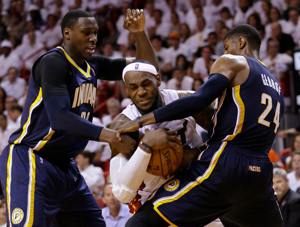 . Indiana Pacers center Ian Mahinmi, left, and forward Paul George (24) attempt to block Miami Heat forward LeBron James during the second half of Game 4 in the NBA basketball Eastern Conference finals playoff series, Monday, May 26, 2014, in Miami. (AP Photo/Wilfredo Lee)