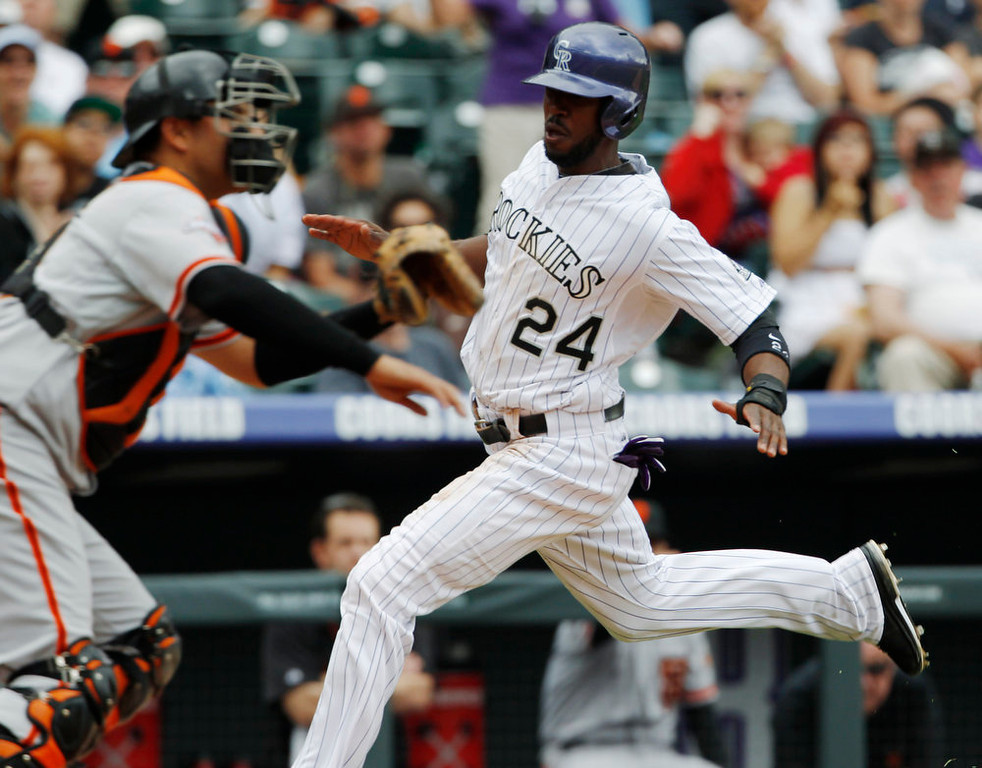 . Colorado Rockies\' Dexter Fowler, back, scores on a double by Carlos Gonzalez as San Francisco Giants catcher Guillermo Quiroz waits for the throw from the outfield in the fifth inning of the MLB National League baseball game in Denver on Sunday, May 19, 2013. (AP Photo/David Zalubowski)