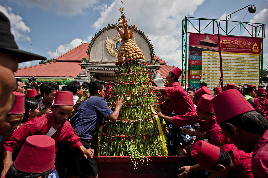 . YOGYAKARTA, INDONESIA - AUGUST 08: Javanese people jostle the \'Gunungan Lanang\' during Grebeg Syawal ceremony on August 8, 2013 in Yogyakarta, Indonesia. Grebeg Syawal is a tradition that follows the holy month of Ramadan to welcome Eid Al-Fitr. The tradition involves an offering of vegetables, peppers, eggs, and other items, called \'Gunungan Lanang\' that are brought to the Grand Mosque and invaded by locals as a symbol of alms from Sri Sultan Hamengkubuwono X to his people. Receiving part of the Gunungan is believed to be good luck and be a blessing for the year ahead. (Photo by Ulet Ifansasti/Getty Images)